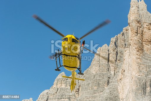istock Yellow helicopter used for rescue operations, Medical rescue helicopter flying rescue injured climber on the Tre Cime. Italy, Dolomites 838214484