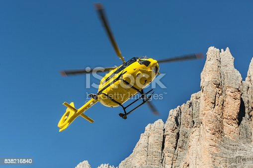 istock Yellow helicopter used for rescue operations, Medical rescue helicopter flying rescue injured climber on the Tre Cime. Italy, Dolomites 838216840