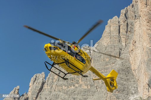 istock Yellow helicopter used for rescue operations, Medical rescue helicopter flying rescue injured climber on the Tre Cime. Italy, Dolomites 838217106