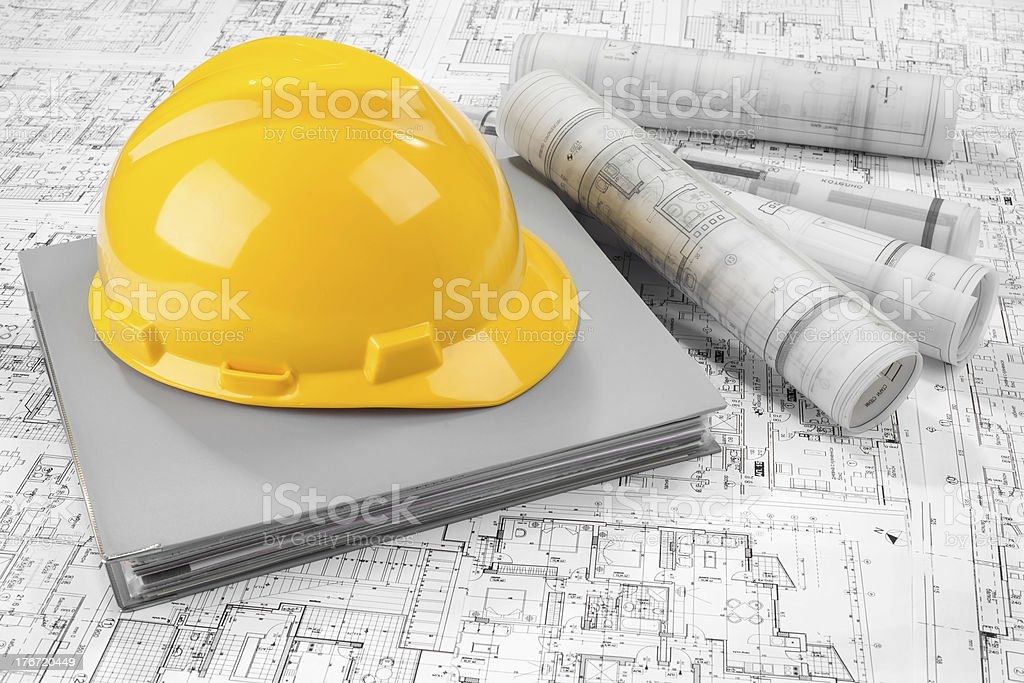 Yellow helmet, grey folder document and project drawings stock photo