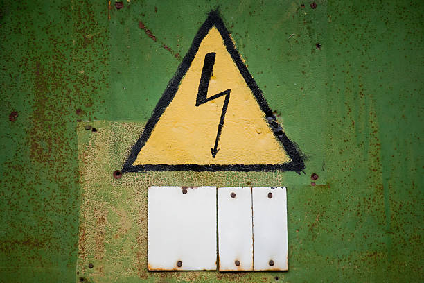 Yellow high voltage sign on aged green textured wall stock photo