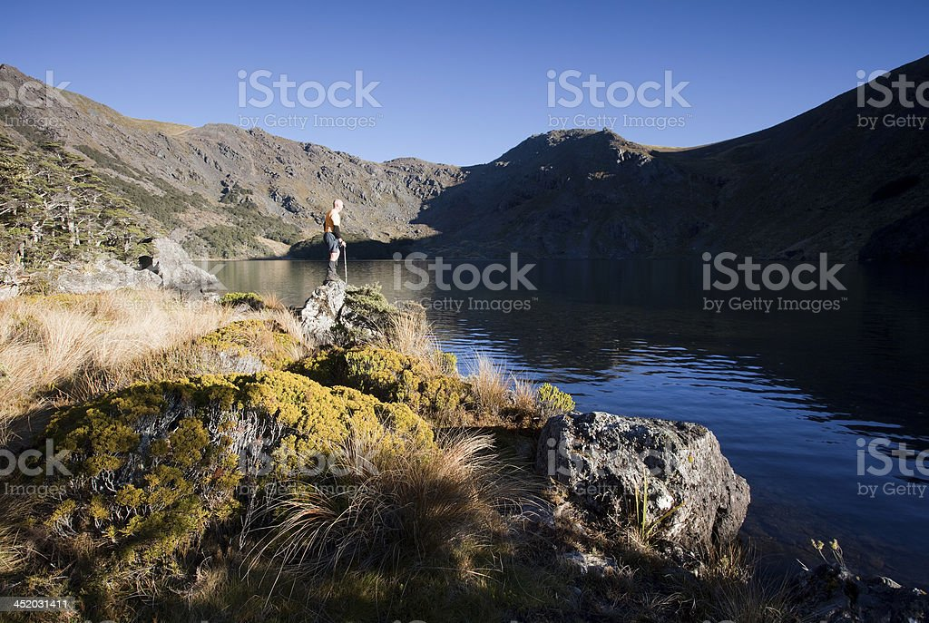 Yellow hiker at remote lake, Kahurangi NP, New Zealand stock photo