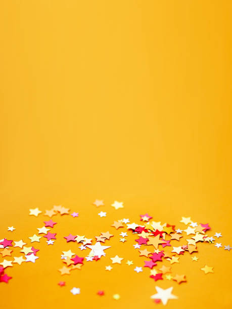 Yellow holiday background with colorful star confetti. Good background for Christmas and New Year cards. stock photo