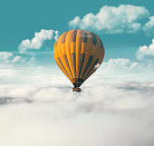 Yellow hot air balloon flying above the clouds