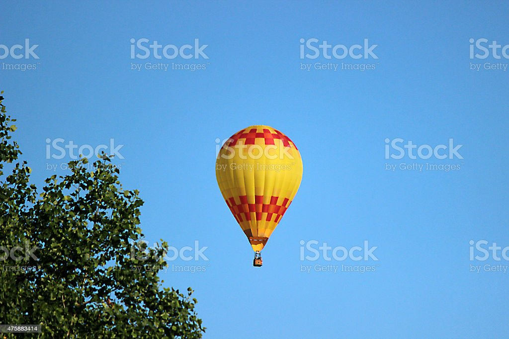 Yellow Hot Air Balloon in Sky with Trees in Foreground stock photo
