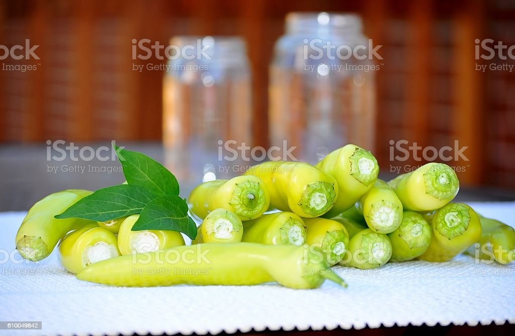 Yellow hot chili peppers and two empty jars. stock photo