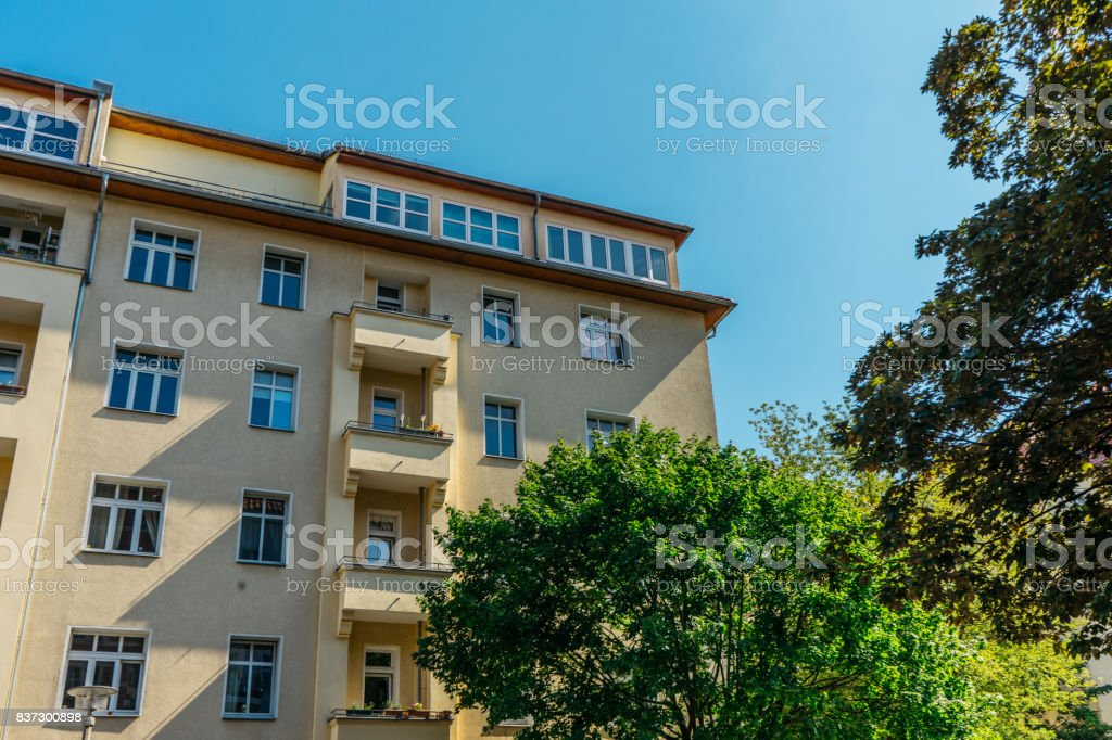yellow house with penthouse in the roof and green tree stock photo