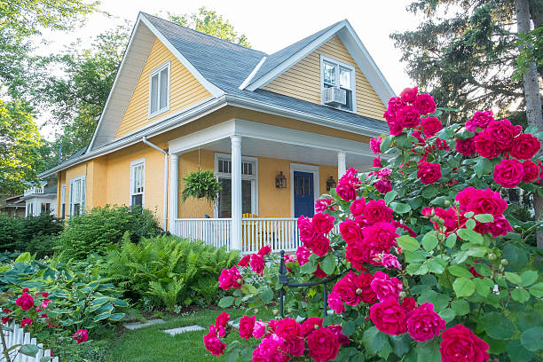 yellow house with pink flowers - house with flowers stock photos and pictures