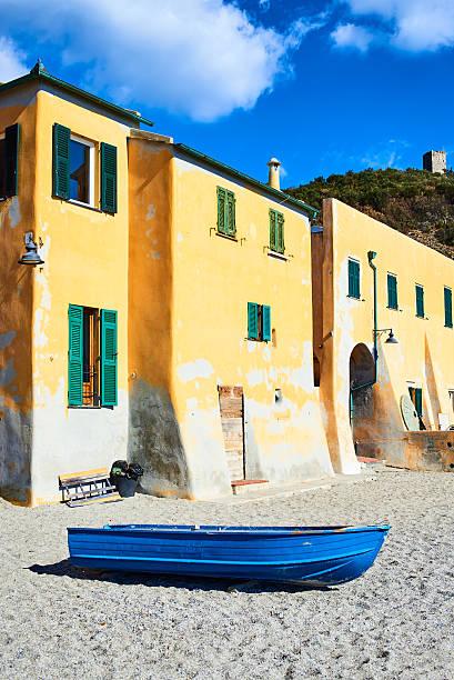 Yellow houses and blue boat on Varigotti beach - foto de stock