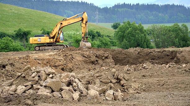 Amarillo excavador hidráulica en proceso de trabajo en masa de tierra - foto de stock