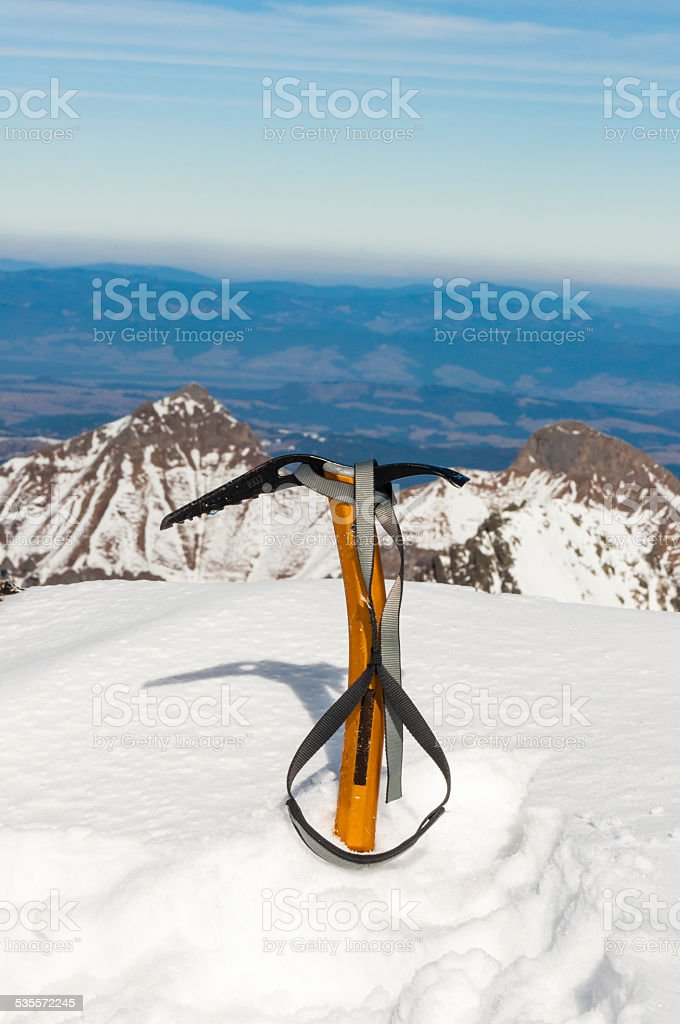 Yellow ice axe in the snow stock photo