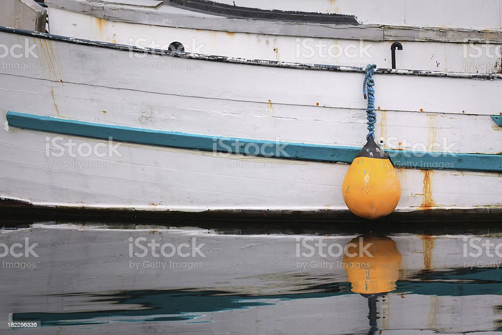 Yellow inflatable bumper protects hull of wooden boat stock photo