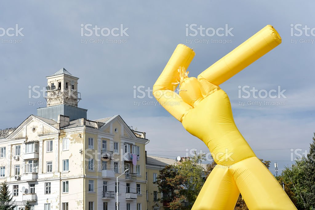 yellow inflatable man on blue sky background stock photo