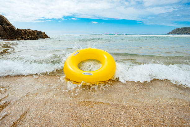 yellow inflatable ring riding a wave at pend vounder beach - rubber ring stock photos and pictures