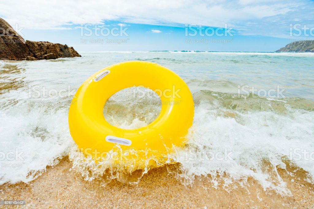 Yellow inflatable ring riding a wave at Pend Vounder Beach stock photo