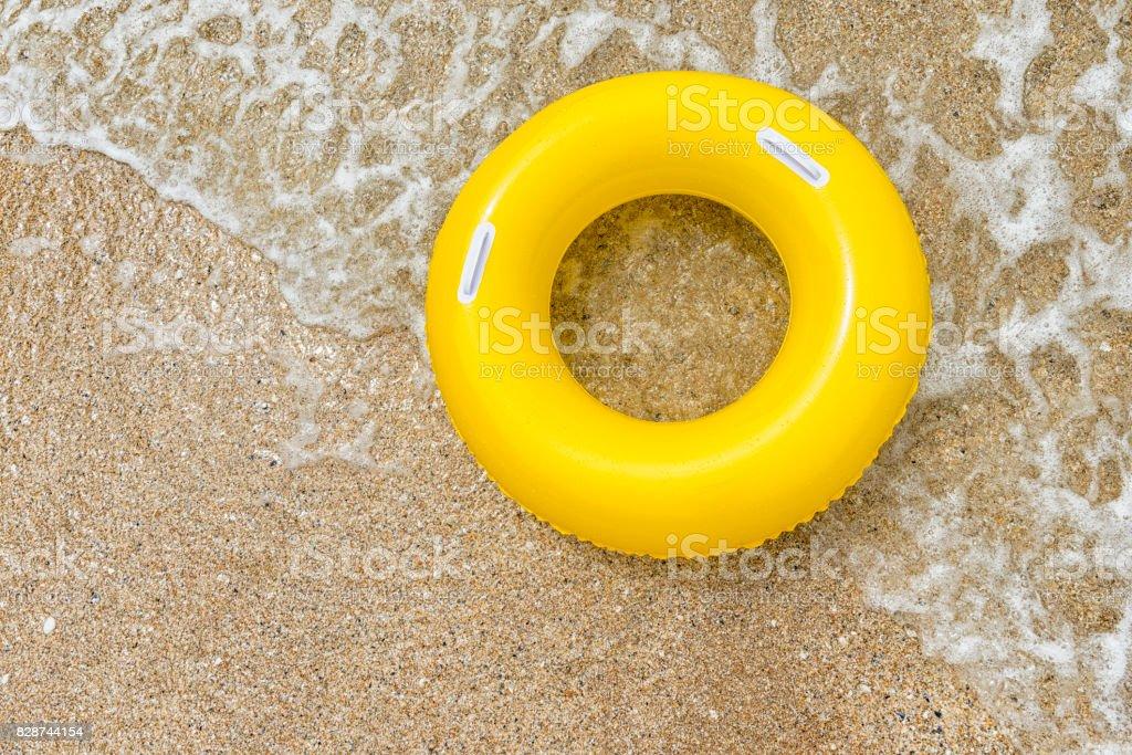 Anneau gonflable jaune, surfant sur une vague sur la plage de Vounder Pend - Photo