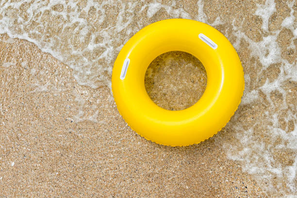 yellow inflatable ring riding a wave at pend vounder beach - rubber ring stock pictures, royalty-free photos & images