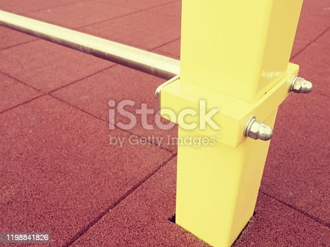 Yellow iron bar on workout playground. The beam holds horizontal acrobatic pole.