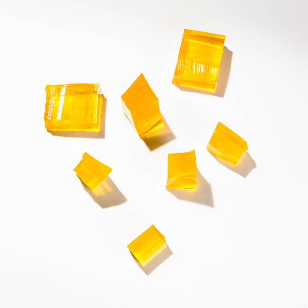 Yellow jelly Misshapen pieces of yellow jelly, isolated on a white background gelatin stock pictures, royalty-free photos & images