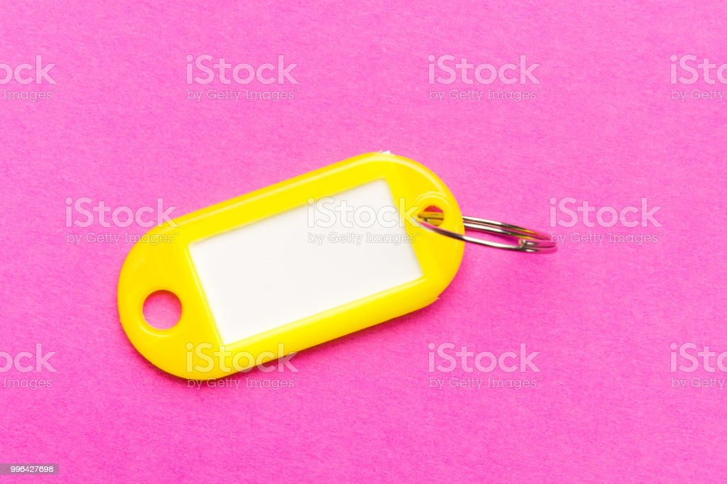 Yellow Key Tag On Purple Cardboard Textured Backgroundthe