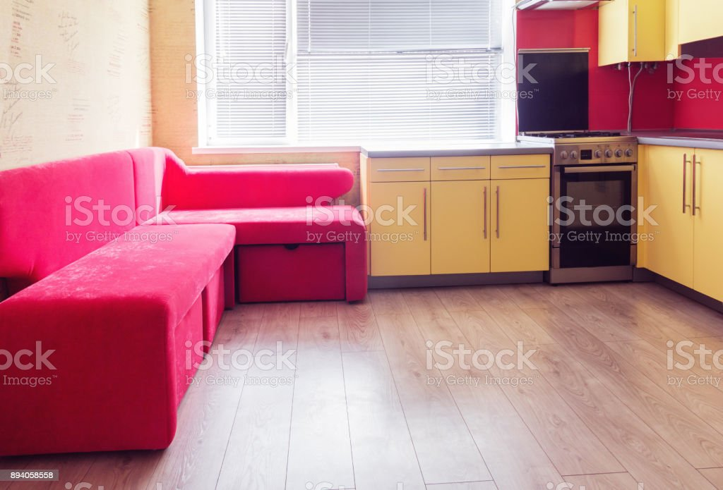 yellow kitchen with cupboards, window, laminate and red soft couch stock photo