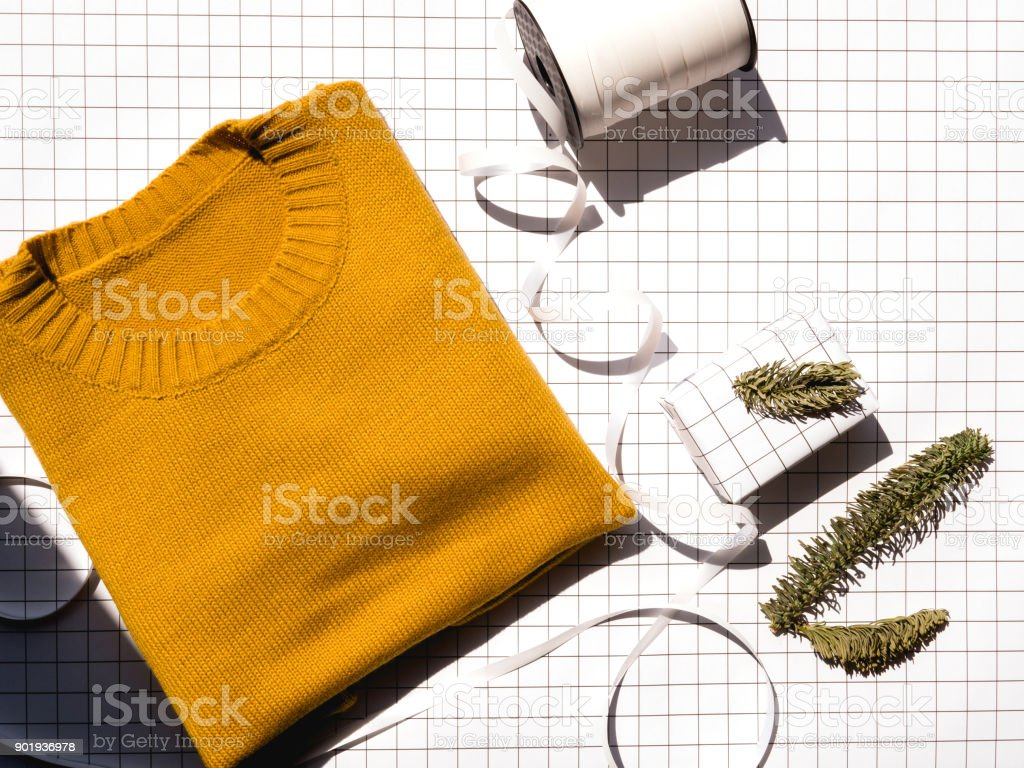 yellow knitting sweater with white gift box and white ribbon to present the winter gift stock photo