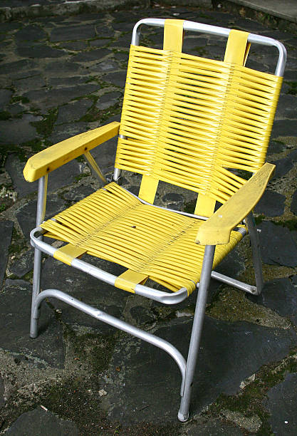 yellow lawn chair on patio stock photo