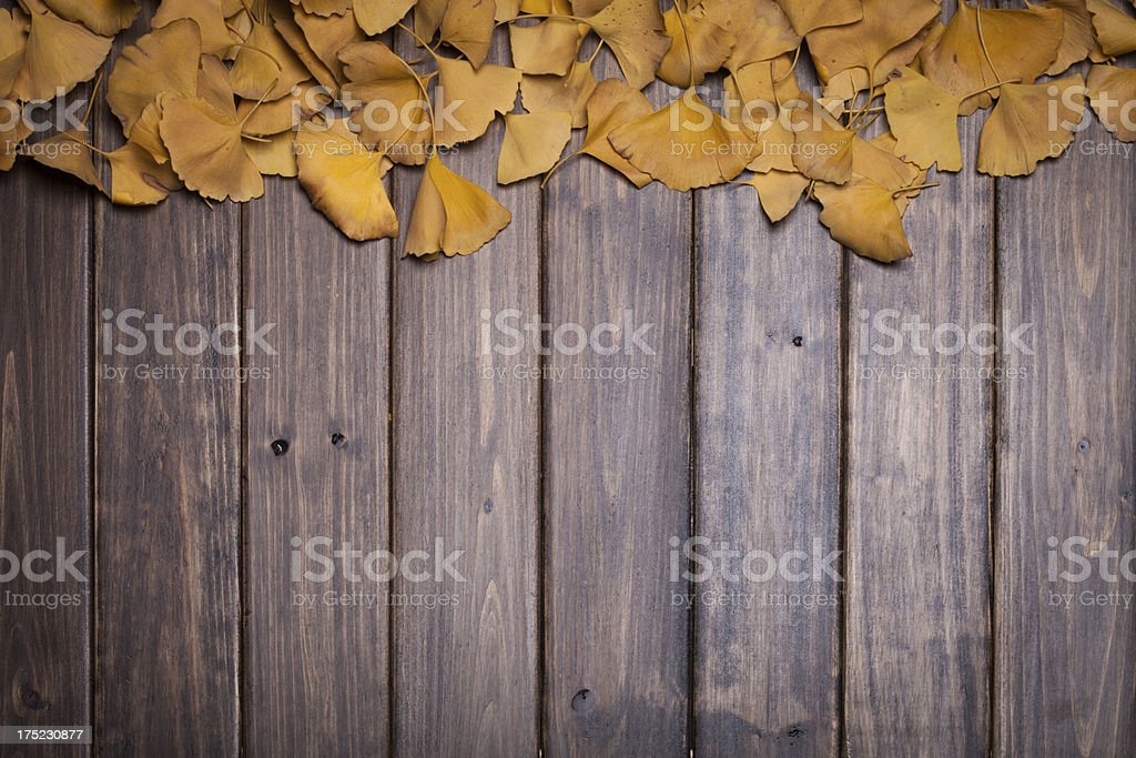 yellow leaf over wooden background royalty-free stock photo