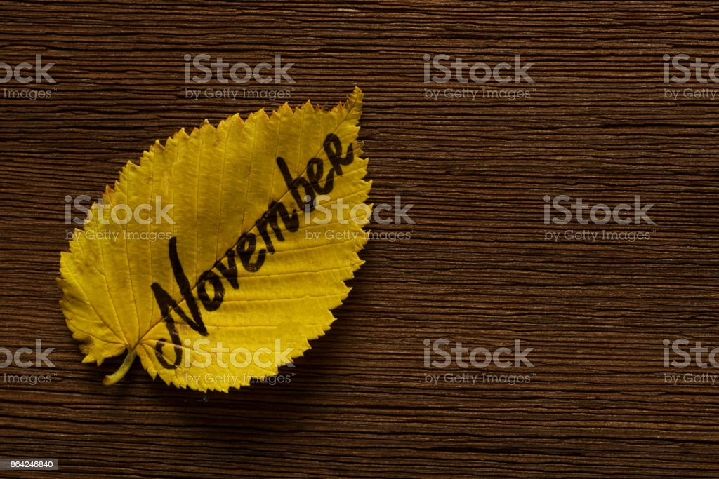 Yellow leaf with inscription NOVEMBER on brown wooden board background. Copy space royalty-free stock photo