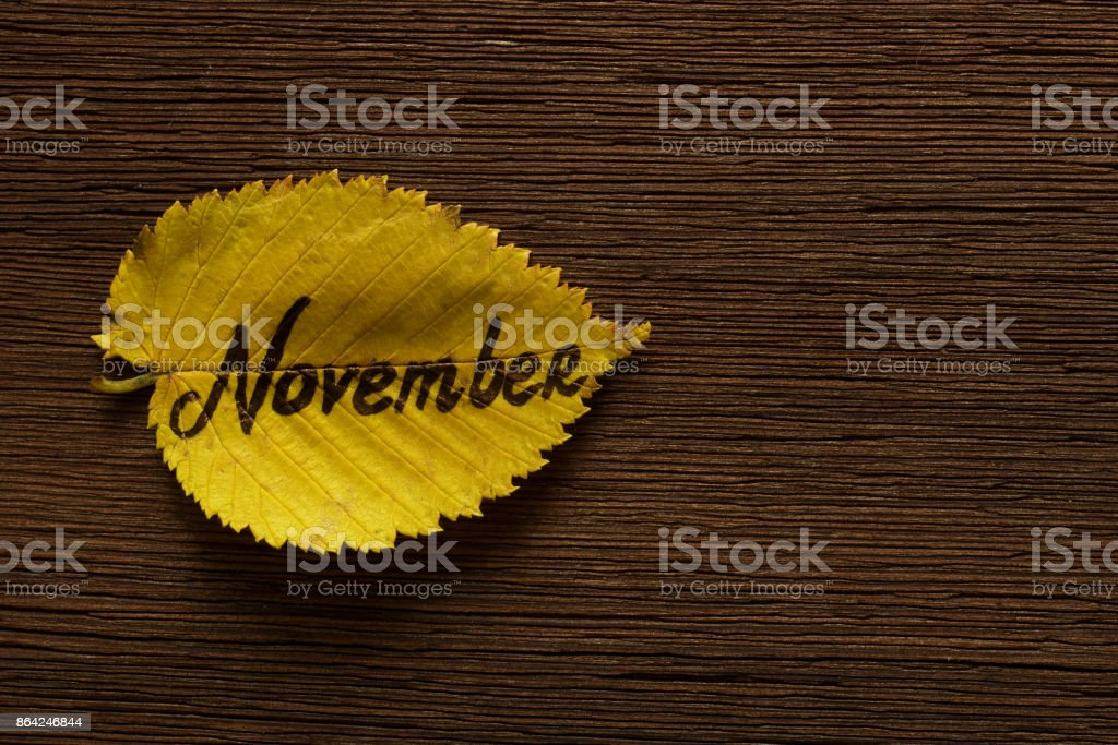 Yellow leaf with inscription NOVEMBER on dark wooden board background. Copy space royalty-free stock photo