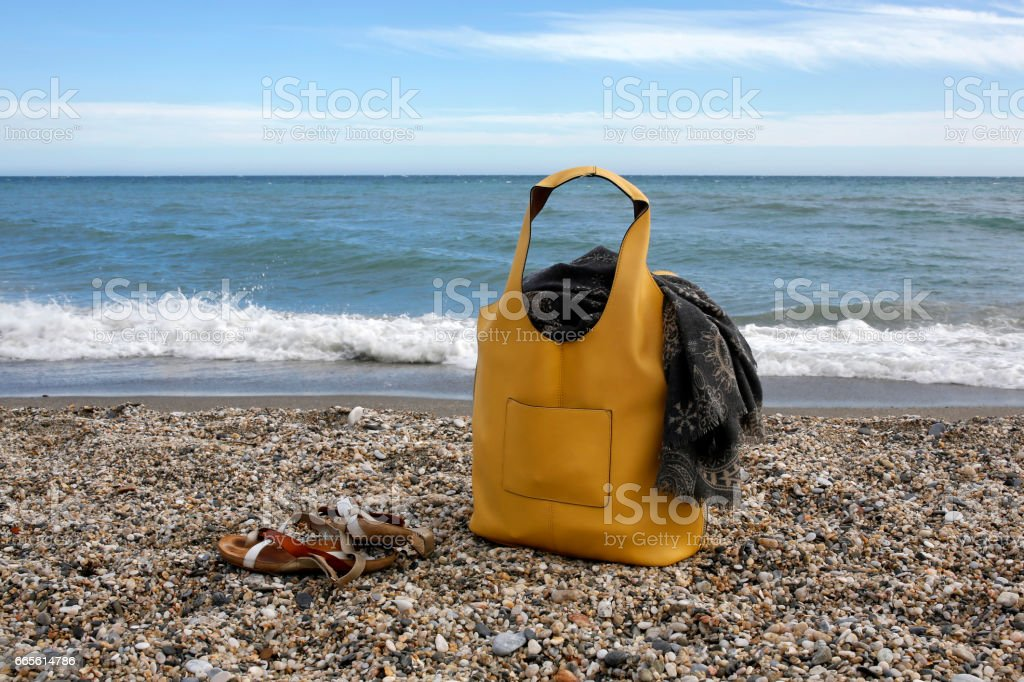 yellow leather bag, scarf and sandals on the beach - foto de stock
