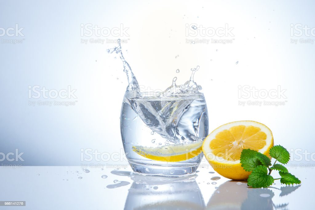 yellow lemons in a glass and splashes of water. Tasty and healthy...