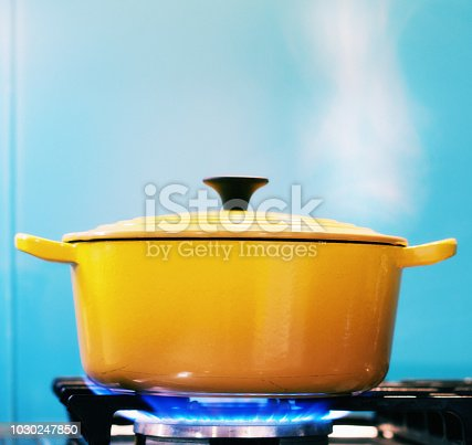 A yellow enamel casserole, with its lid on, sits on a lit gas burner creating steam as it heats.
