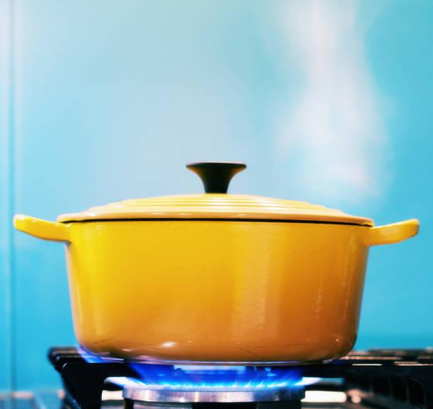 yellow lidded pot steaming on lit gas stove - caçarola imagens e fotografias de stock