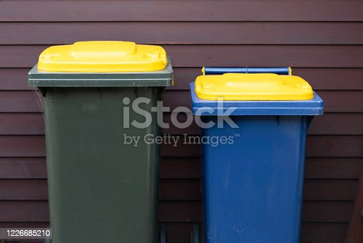 Yellow lids on a recycling bin and a garbage bin