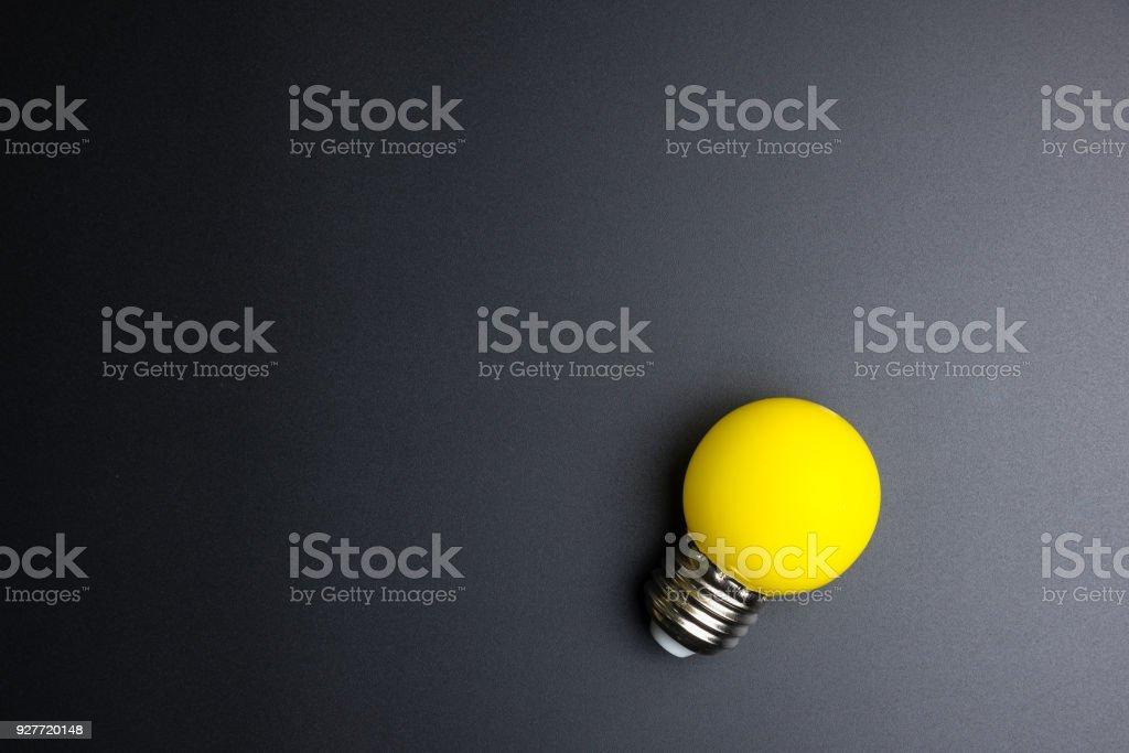 Gelbe Glühbirne auf schwarzem Hintergrund mit Textfreiraum. – Foto