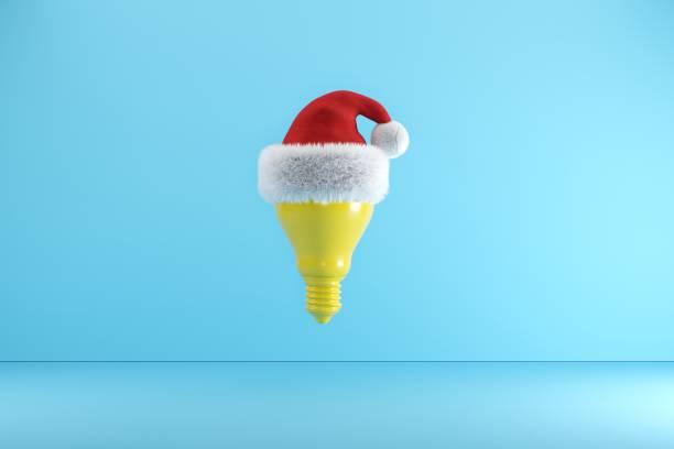 Gelbe Glühbirne mit Santa Hut schwebenauf auf blauem Hintergrund, Weihnachtskonzept Ideen, 3D-Illustration. – Foto