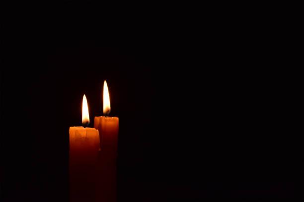 vela amarillo de la luz arde brillantemente en el fondo negro. - memorial day fotografías e imágenes de stock