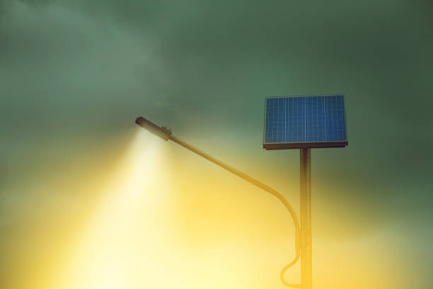 yellow light from street lighting pole with photovoltaic panel at evening, renewable energy for public stock photo