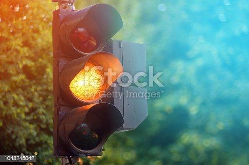 Yellow light of traffic lights in summer city