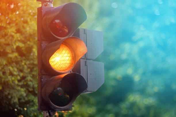 yellow light of traffic lights in summer city - railway signal stock photos and pictures