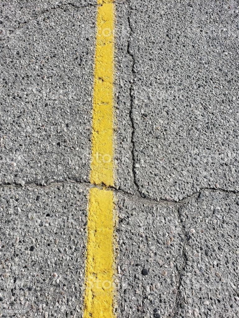 Yellow line on cracked asphalt