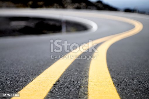 A double yellow line on a road curving into the distance.