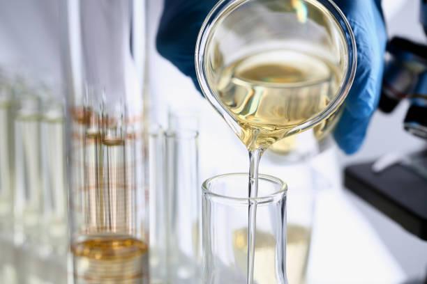 fuente innovador aditivo gasolina derramado líquido amarillo - química fotografías e imágenes de stock