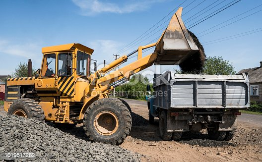 Yellow loader delivering stone gravel into truck during road construction works. The stones for the road. Unloading stone
