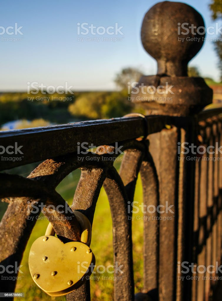 Yellow lock in shape of heart hangs on old rusty fence at sunny day royalty-free stock photo