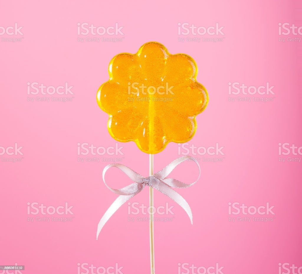 Yellow Lollipop On Pink Background stock photo