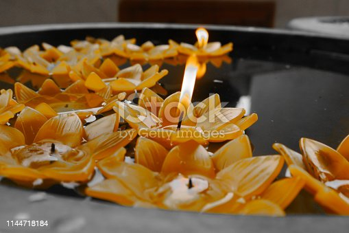 Yellow lotus flower candle in the basin
