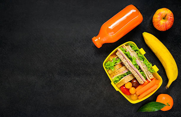Yellow Lunch Box with Food on Copy Space stock photo