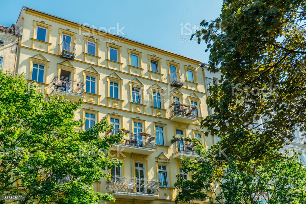 yellow luxury facade with green trees stock photo